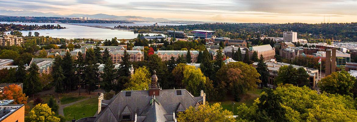 An aerial photo above Denny Hall on the UW campus with a distant Seattle skyline