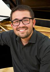 Nicholas Tagab smiling to camera, while leaning against a piano
